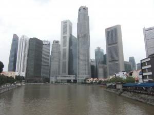 Am rechten Bildrand kann man noch erahnen, wie Singapur einst ausgesehen hat. Dahinter strecken sich die Giganten der Neuzeit in den tropischen Gewitterhimmel.